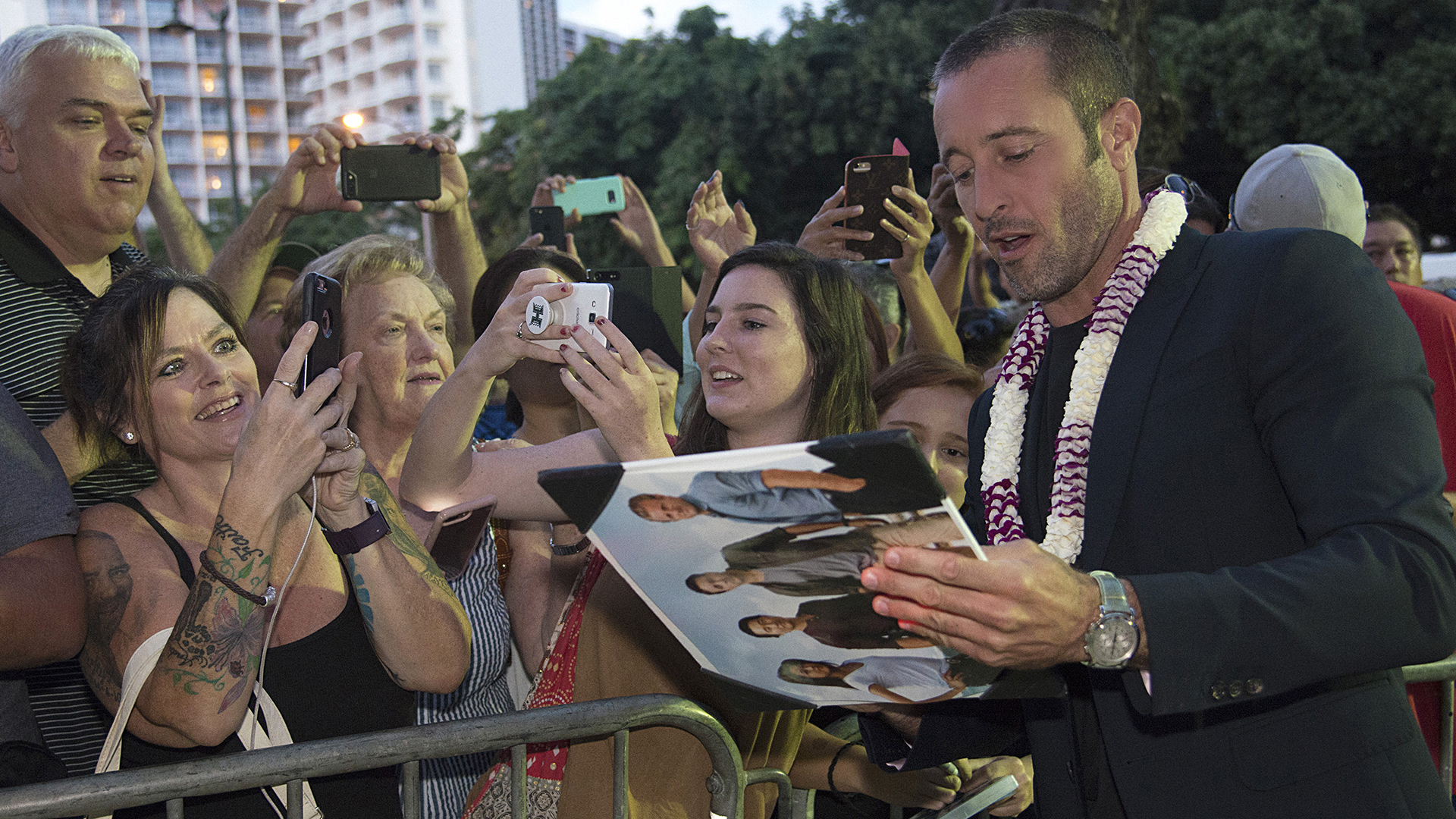 Alex O'Loughlin autographs show art for fans while walking the red carpet.