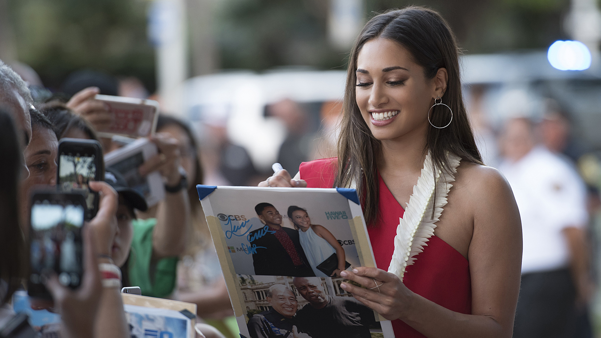 Meaghan autographs fan posters while walking the Sunset on the Beach red carpet.