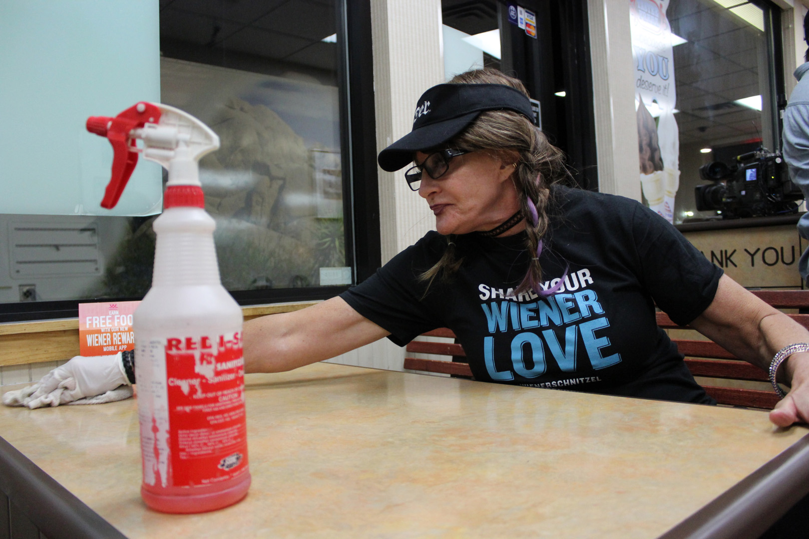 Cynthia wipes down a table while undercover at a Wienerschnitzel location.